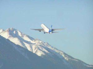 Ein Flugzeug startet vom Innsbrucker Flughafen in Richtung der schneebedeckten Berge